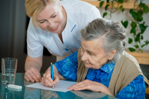 nurse helping client on writing