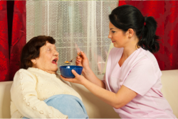 caretaker assisting her old patient in eating